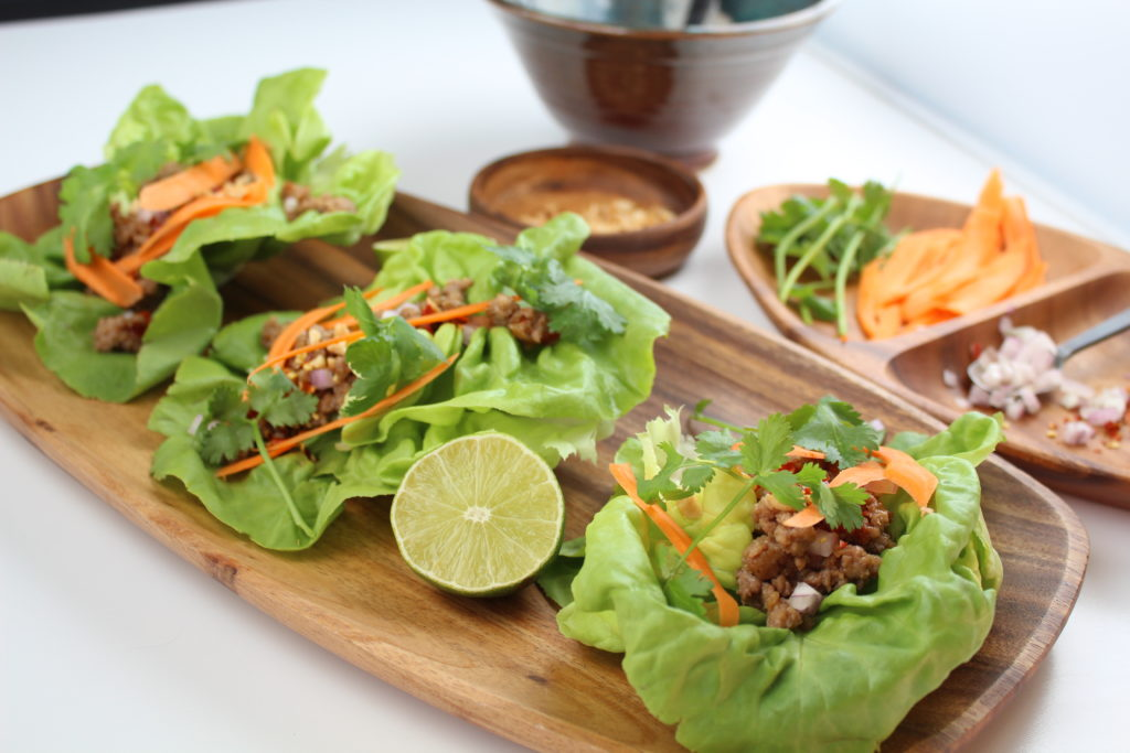 3 lettuce wraps on a wooden plate with lime