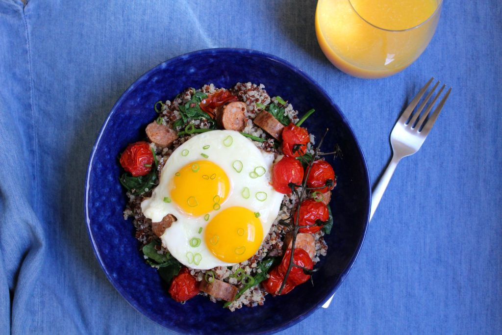 sunny side up eggs over quinoa in a blue bowl