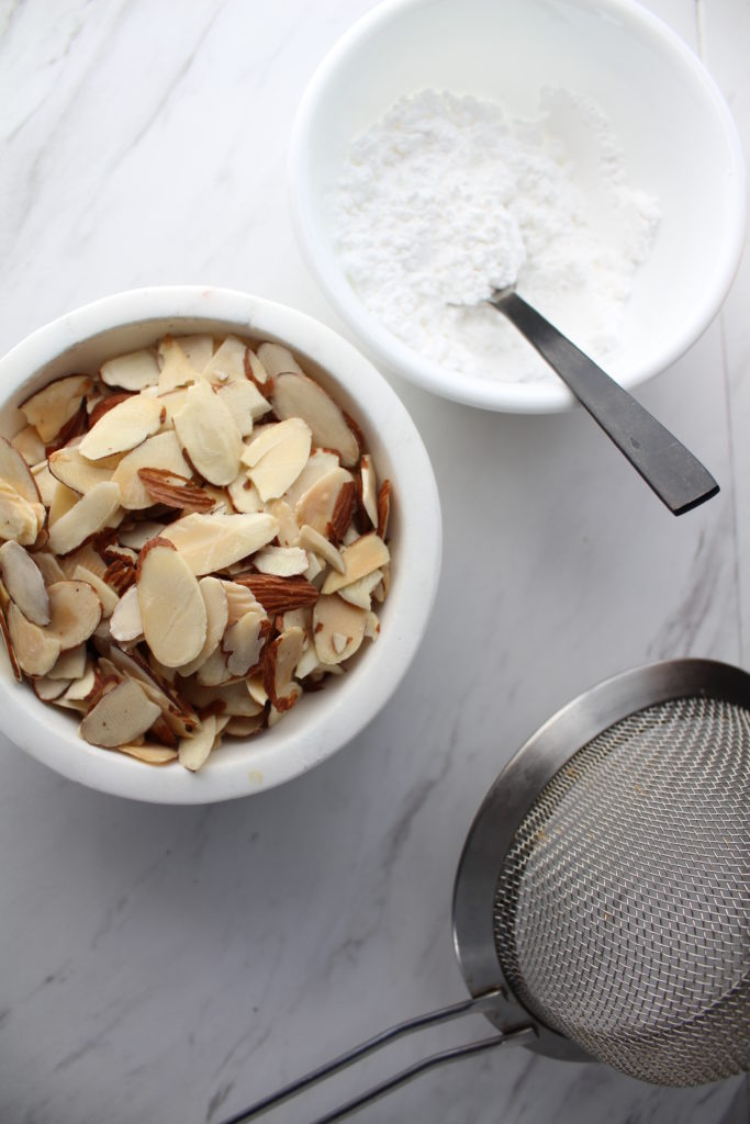 slivered almonds in a bowl nex to a bowl of powdered sugar