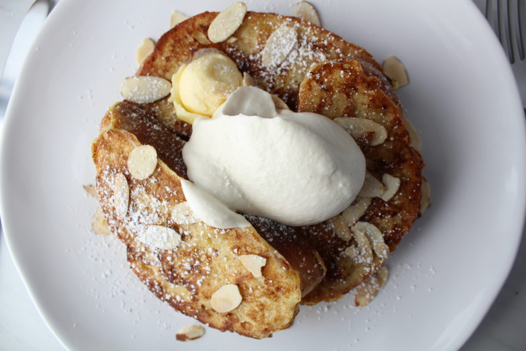 french toast with a dollop of maple whipped cream and butter