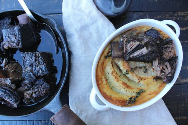wine braised short ribs in cast iron skillet next to mashed potatoes with herbs