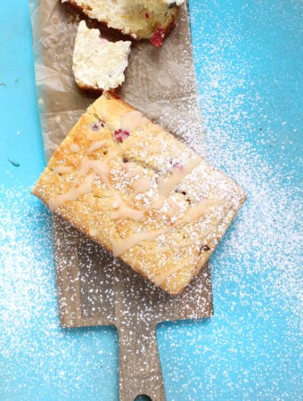 cranberry orange bread with blue background and powdered sugar