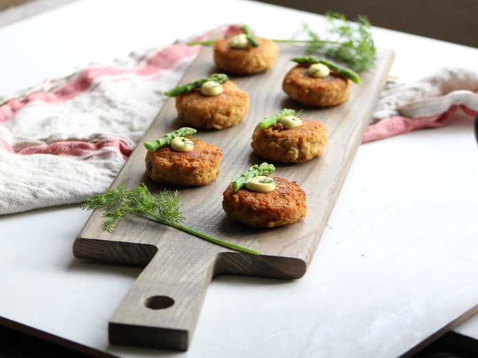 salmon cakes served on a board with dill
