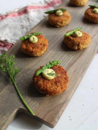 salmon cakes on a serving board with asparagus and dill garnish