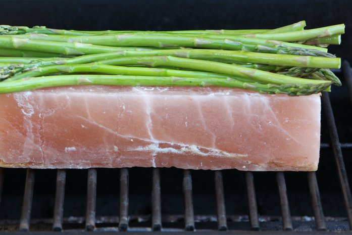 asparagus being cooked on a salt block