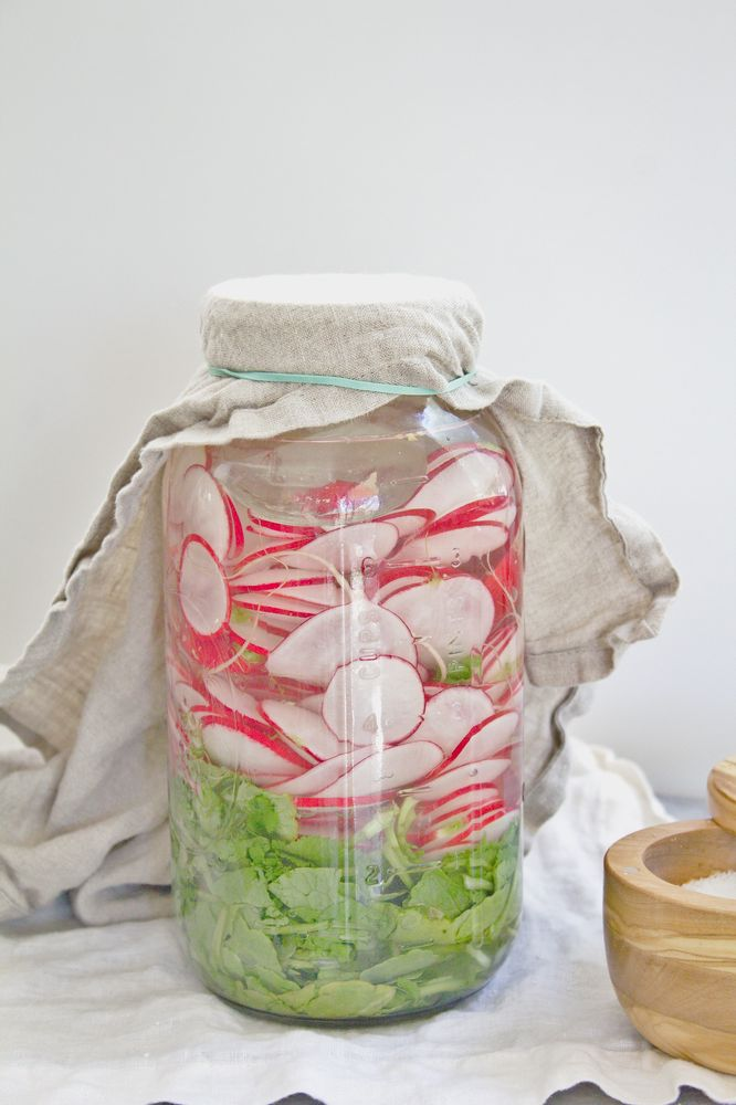 radishes and greens in fermentation jar