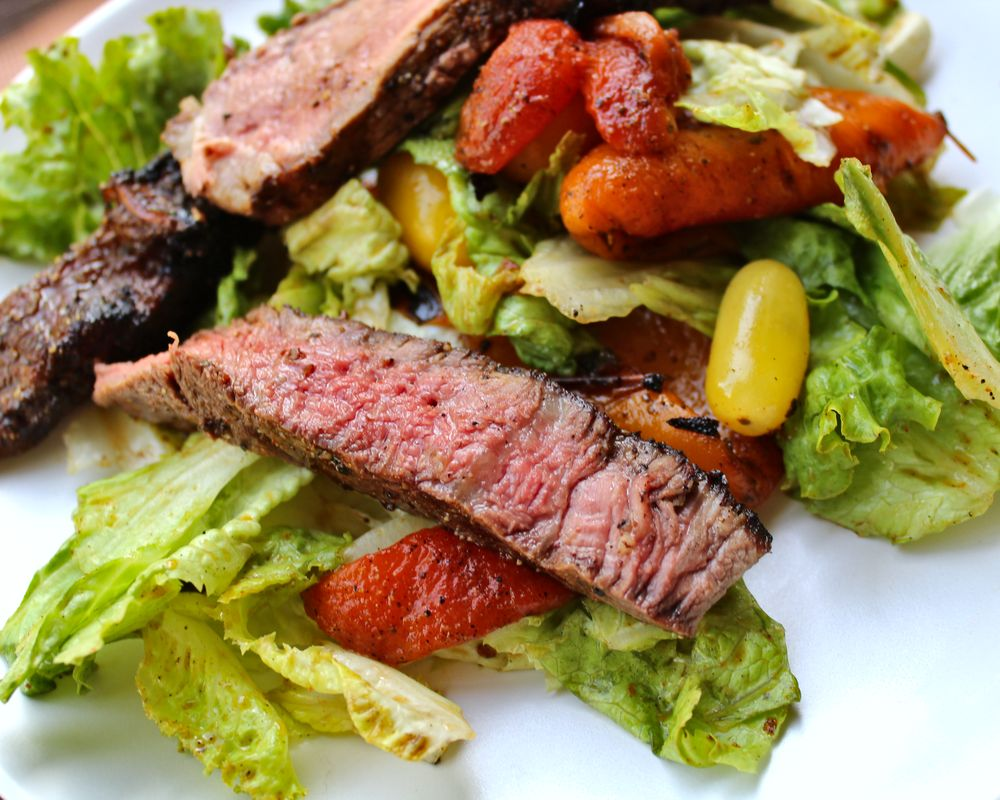 steak salad featuring rib eye, tomatoes, and fire roasted bell peppers with spiced vinaigrette dressing