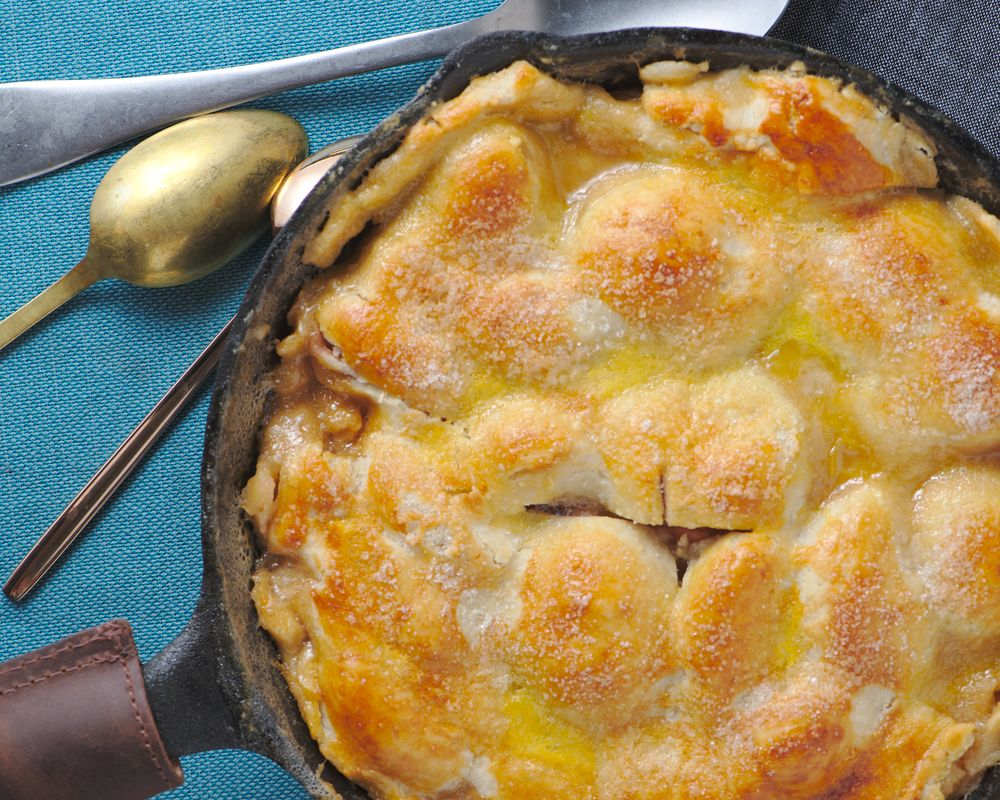 peach cobbler with pie crust in cast iron skillet
