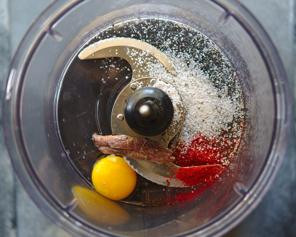 food processor with egg yolk, anchovy, smoked paprika, and salt
