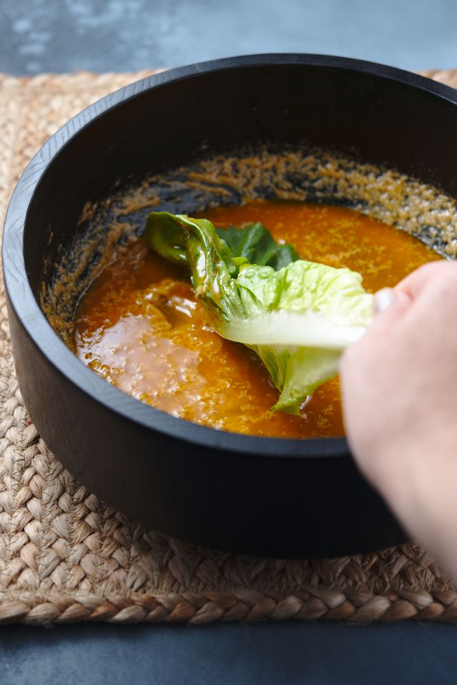 rolling the romaine leaves in a wooden bowl with caesar dressing