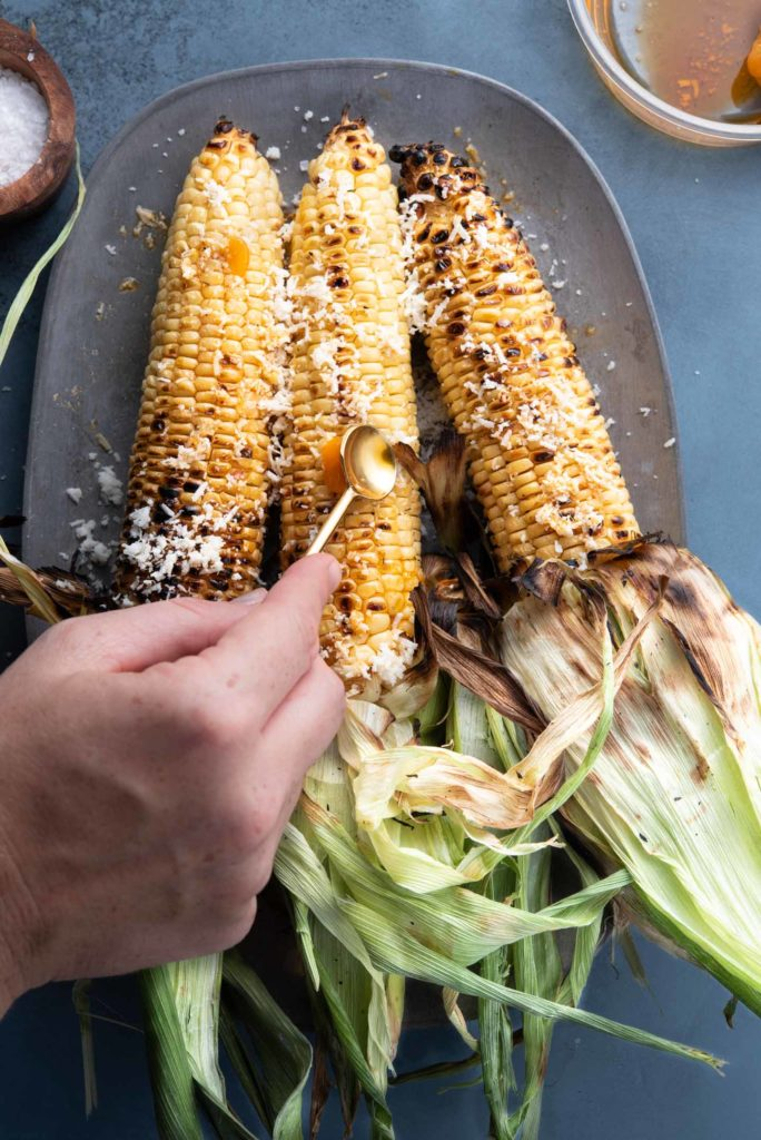 topping the corn with chili infused oil