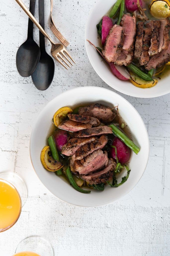 duck breast with green onion pan sauce and summer vegetables in a bowl