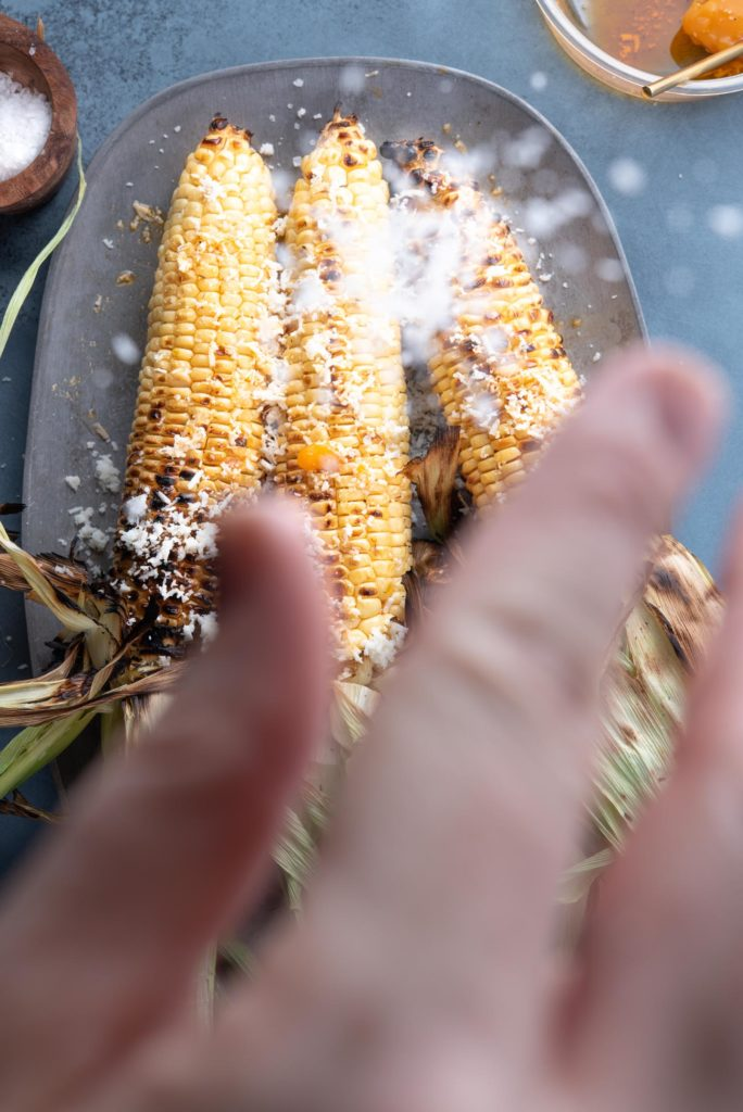 seasoning the corn with cotija cheese