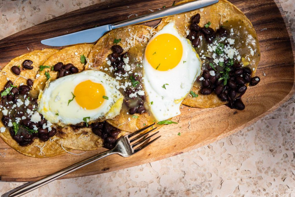 sunny side up eggs over tortillas with black beans and salsa verde