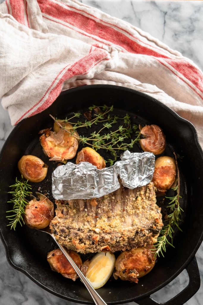 oven roasted rack of lamb with potatoes in cast iron skillet with rosemary and thyme