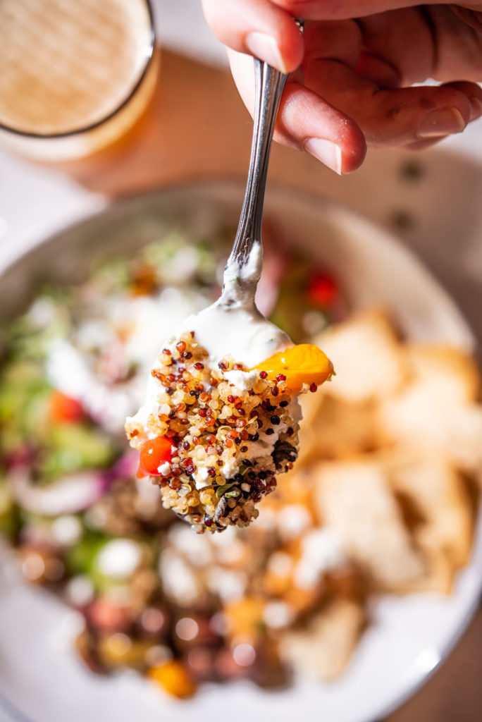 quinoa on a spoon with yogurt sauce and Greek peppers