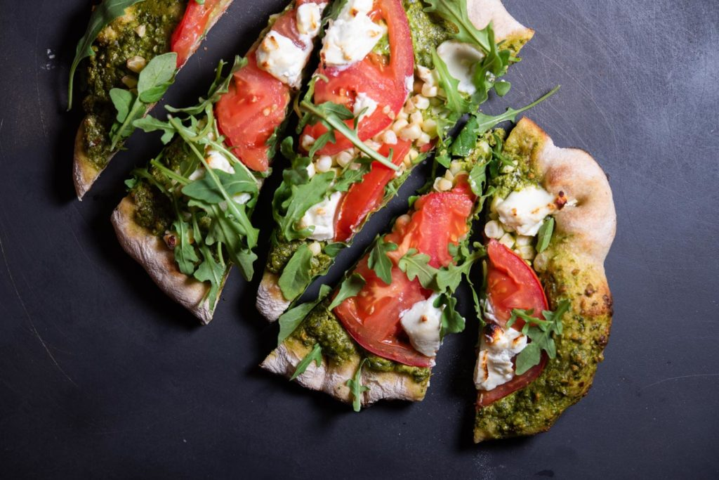 grilled flatbread with goat cheese, tomato, arugula, corn and pesto toppings