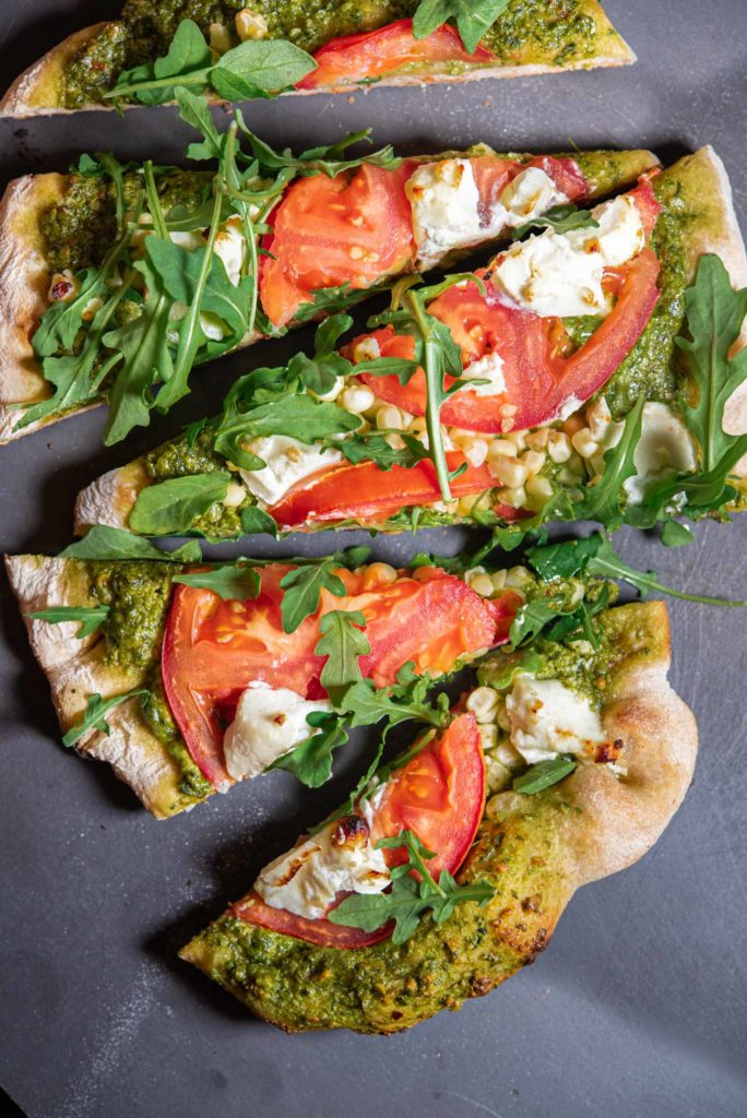 crunchy flatbread with tomatoes, corn, arugula, pesto, and corn