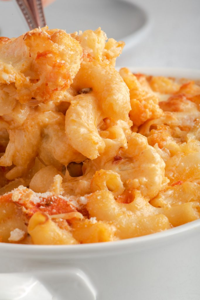 macaroni and cheese in a baking dish with buffalo sauce and cauliflower