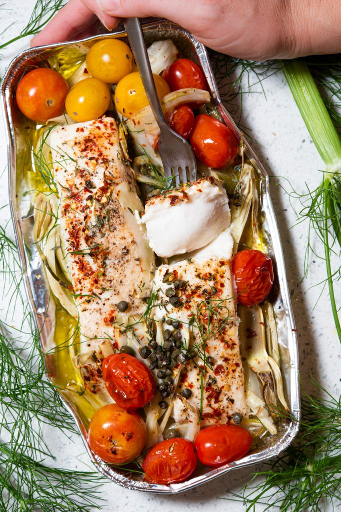 white fish in a foil pack with white wine sauce and vegetables