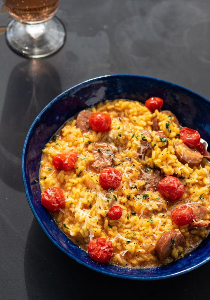 saffron risotto garnished with blistered cherry tomatoes and fresh thyme and parsley