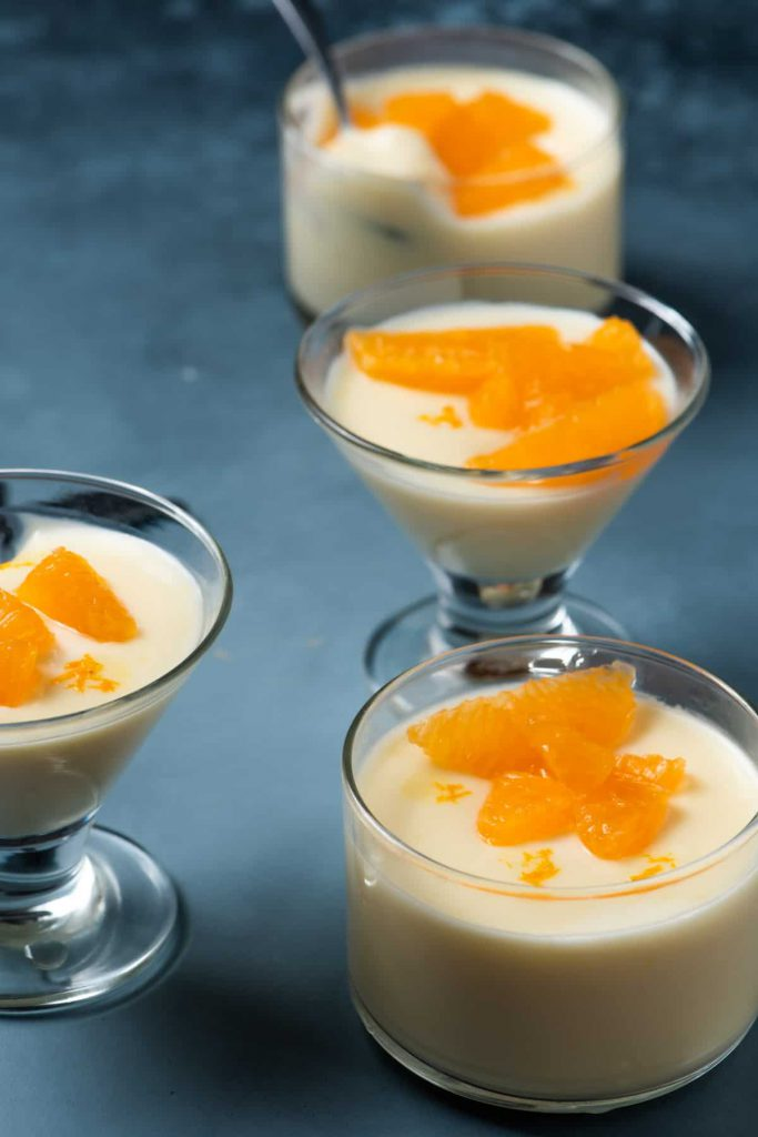 possets served in glasses with tangerine garnish