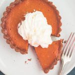 vegan gluten free pumpkin pie on plate with whipped cream