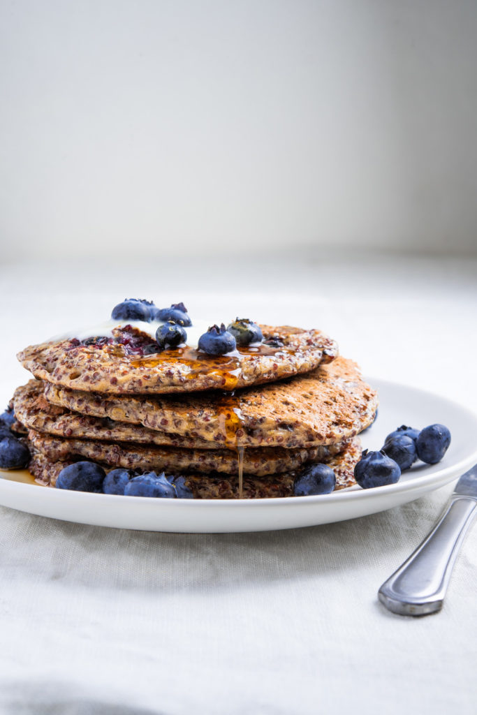 stacked johnny cakes made with red quinoa, blueberries, yogurt, and maple syrup