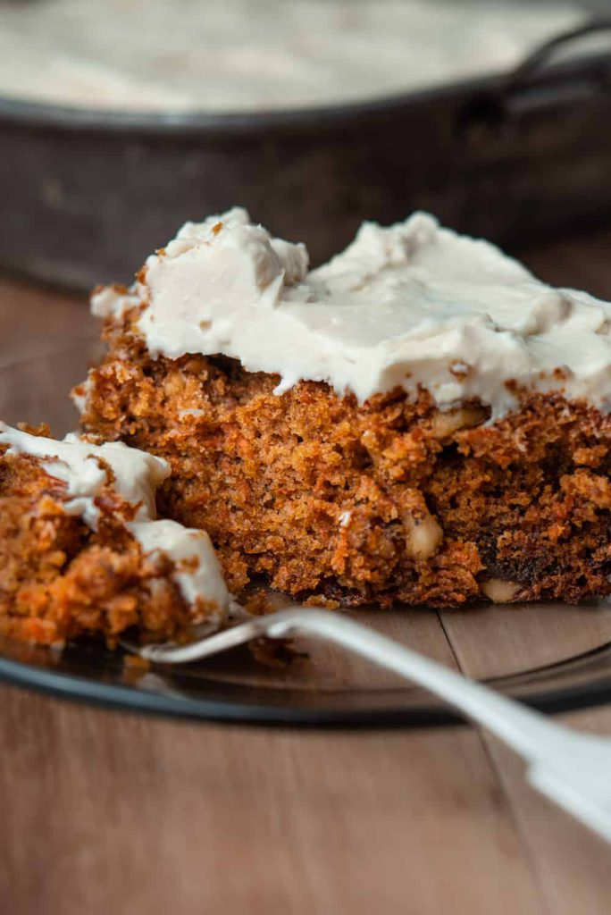 slice of carrot cake on a plate with cream cheese frosting