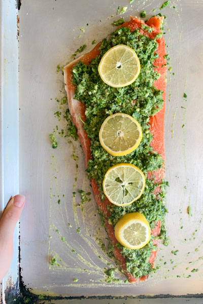 raw salmon fillet with skin topped with fresh herbs and lemon
