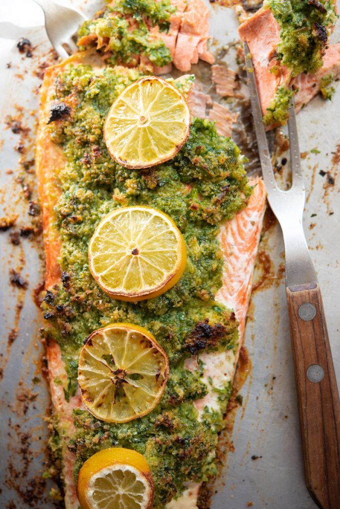 baked salmon on a sheet tray with parsley garlic crust and lemon slices