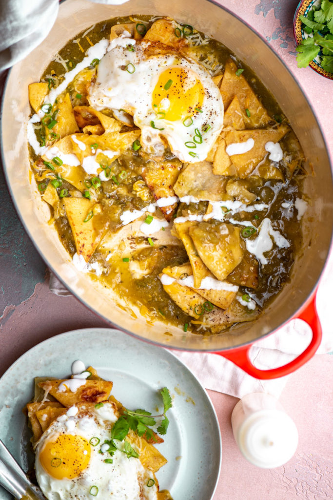 chilaquiles with green enchilada sauce and fried eggs, sour cream, and fried tortilla