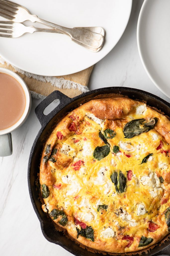 frittata with feta, basil, sausage, and roasted bell pepper in cast iron skillet