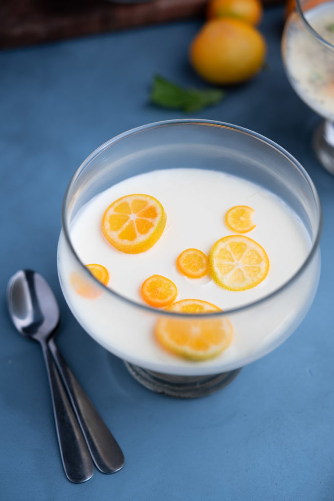 chilled lemon posset served in a glass with kumquats on top