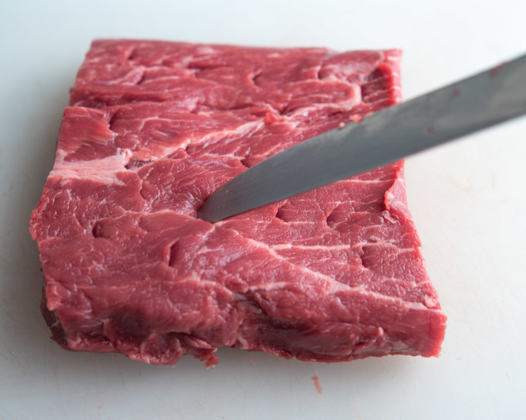 flank steak being pierced with a knife at an angle