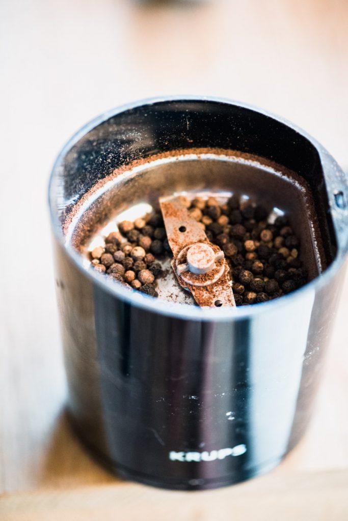 black peppercorns in spice grinder