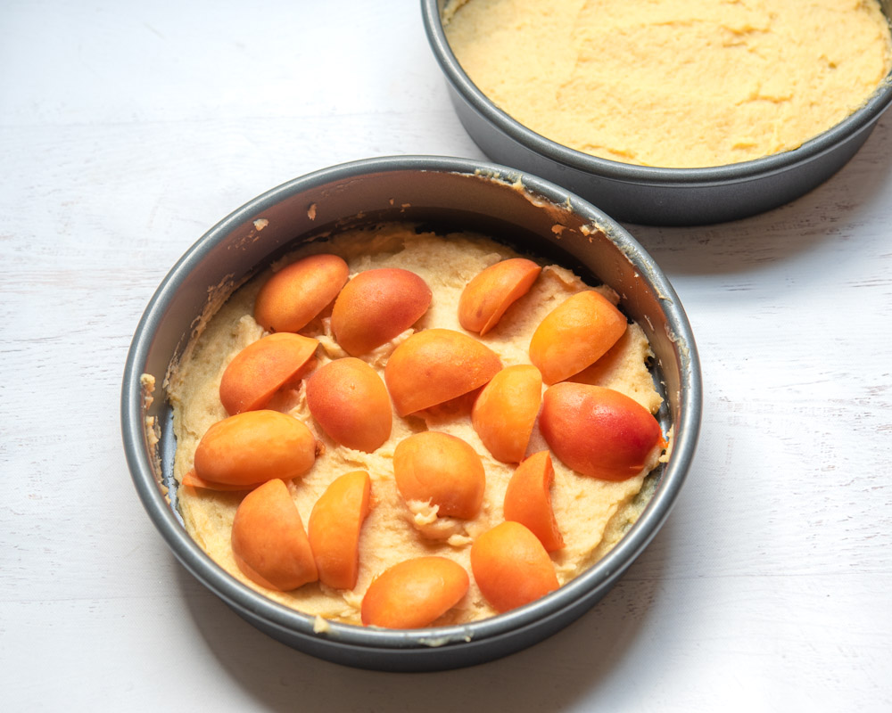 apricots pressed on top of choux pastry in cake pan