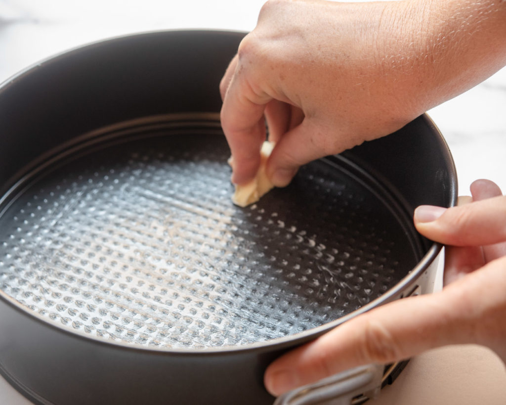 greasing a springform pan with butter