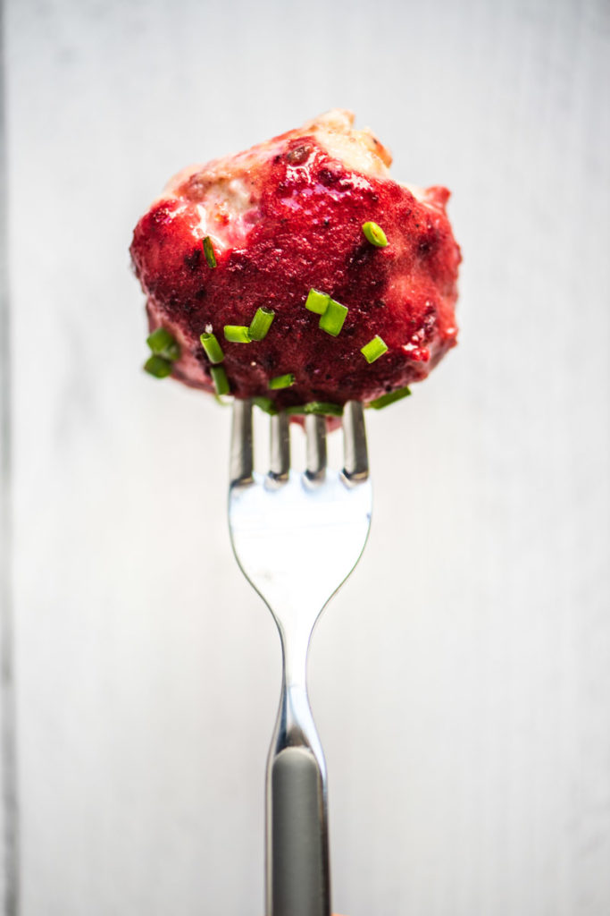 chicken meatball on fork with plum sauce