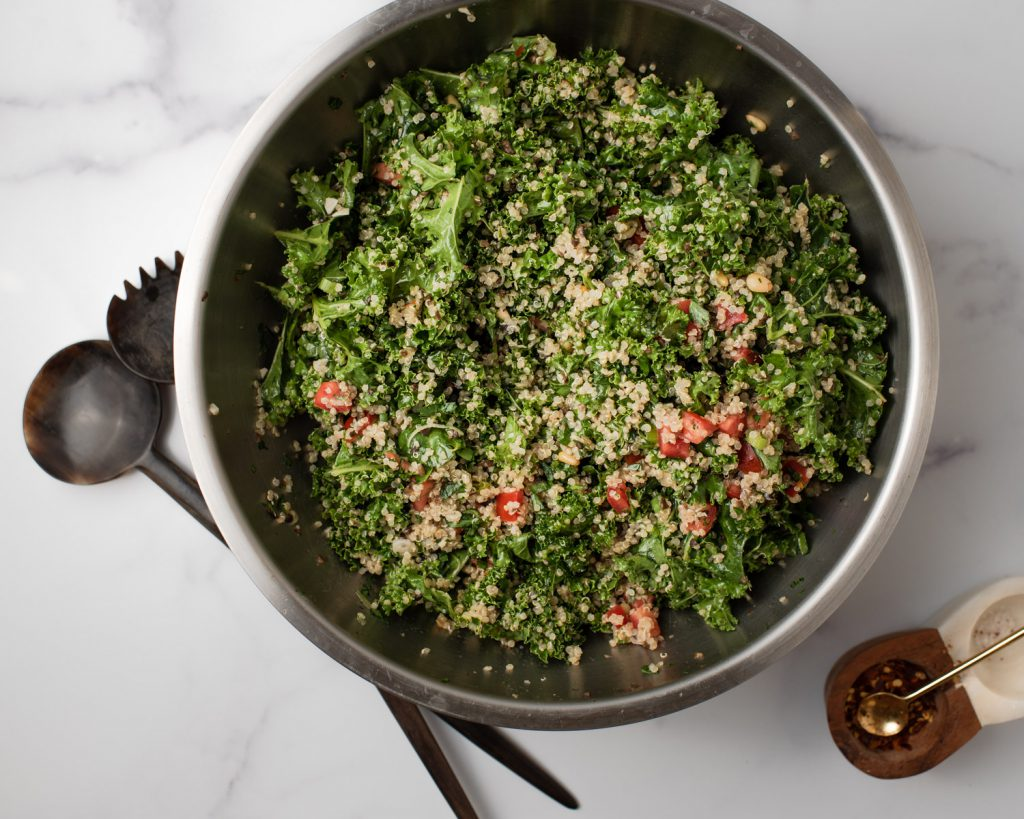 quinoa and kale salad tossed in a bowl