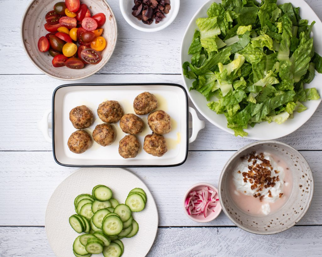 turkey meatballs in baking dish with chopped romaine and chopped vegetables