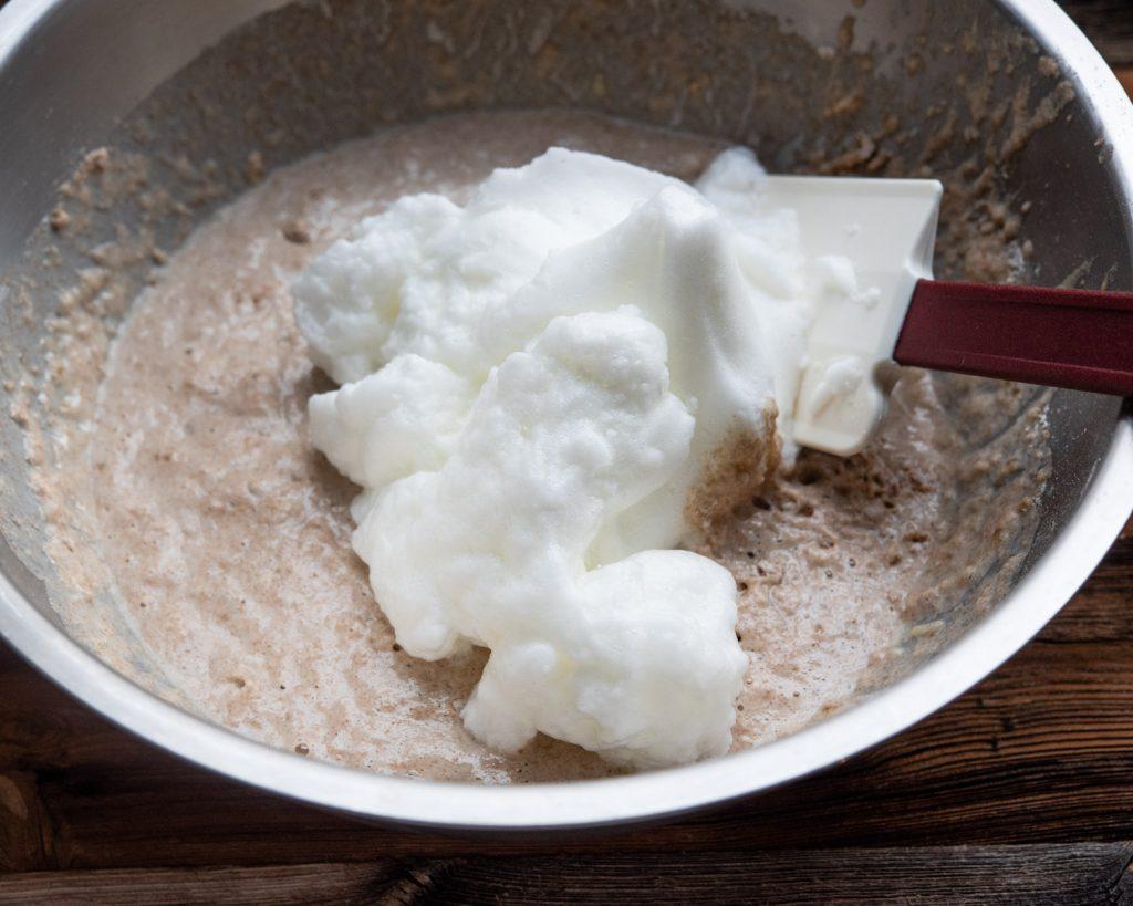 foamed egg whites being folded into homemade waffle batter