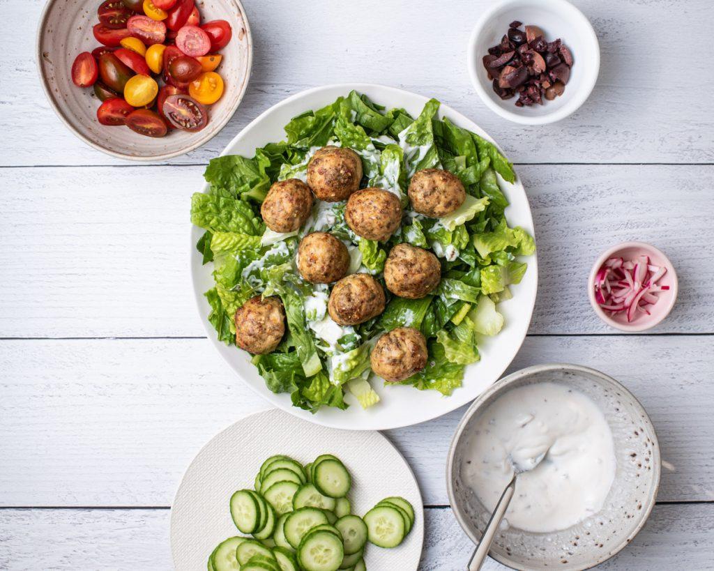 baked turkey meatballs arranged over salad greens