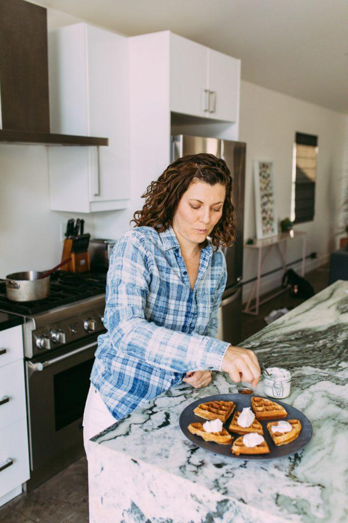 garnishing homemade waffles with whipped cream and cinnamon
